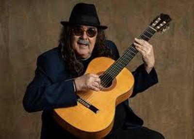 O cantor Moraes Moreira com chapéu e óculos e violão na mão