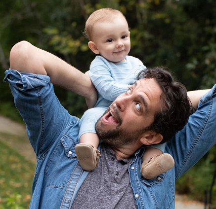 Nick com o filho de 10 meses nas costas