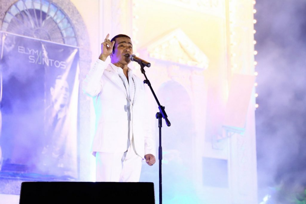 De branco Elymar Santos canta na igreja da Penha