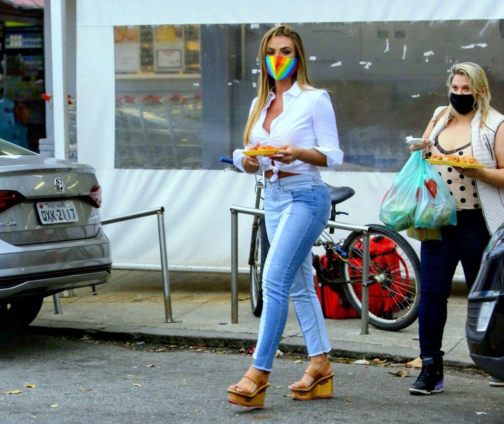 Nicole Bahls faz compras enquanto marido troca pneu do carro.